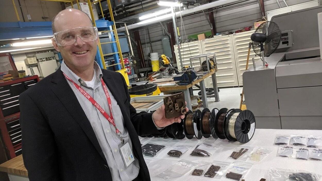 Plan moyen de Darrel Fry debout dans une usine présentant le logo de son entreprise.