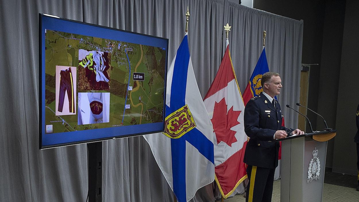 Un policier fait un point de presse près d'un écran qui affiche une carte satellitaire et des photos d'un uniforme de police.
