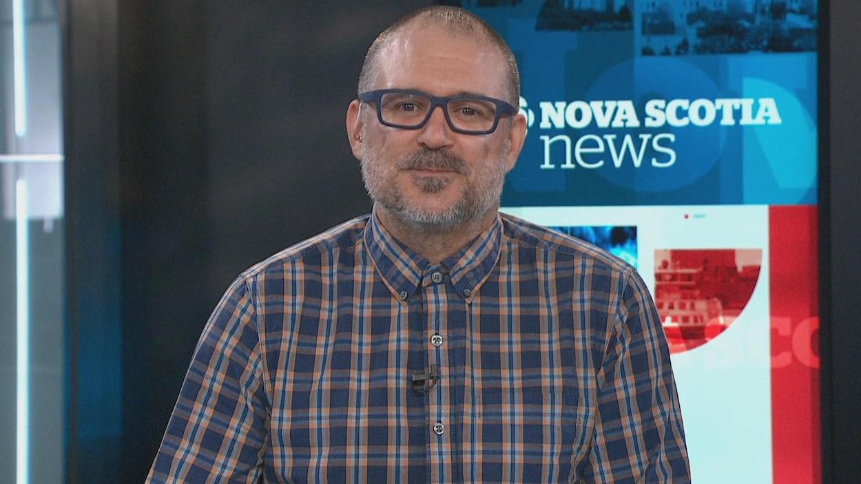 Un homme avec des lunettes bleues devant une caméra de télévision.