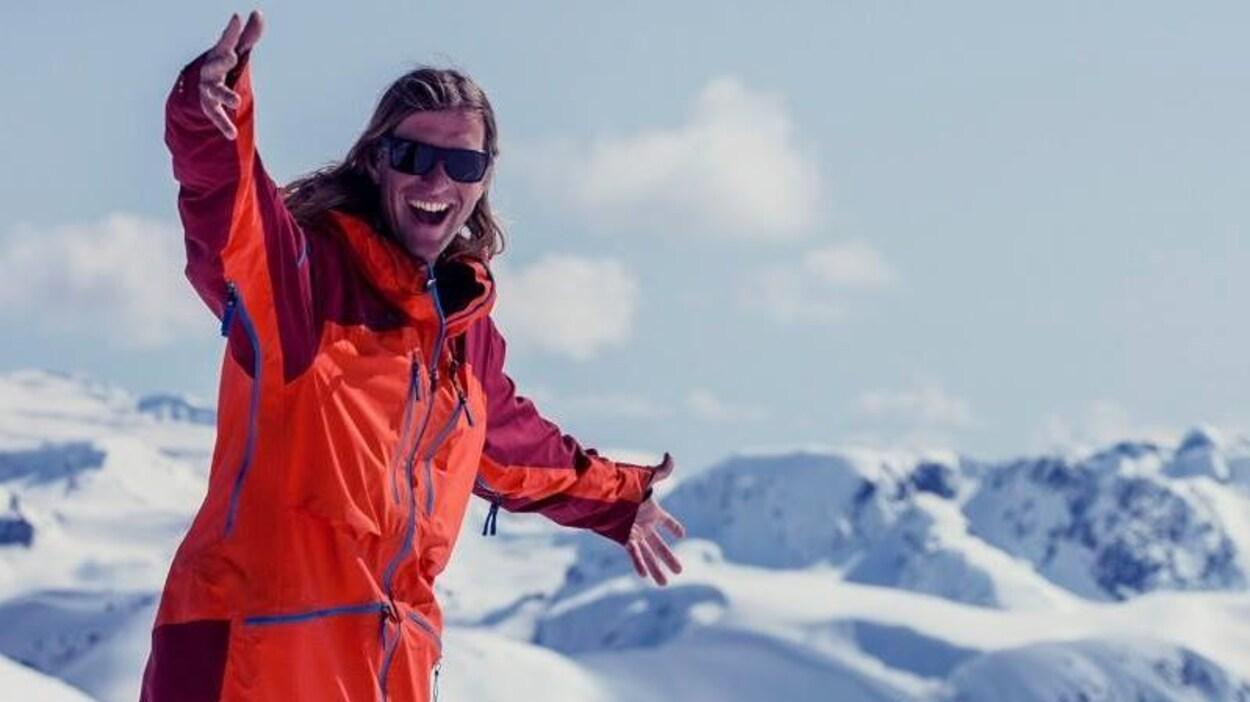 Un homme regarde vers la caméra en souriant, il a un manteau d'hiver, il se trouve sur un sommet de montagne enneigé.