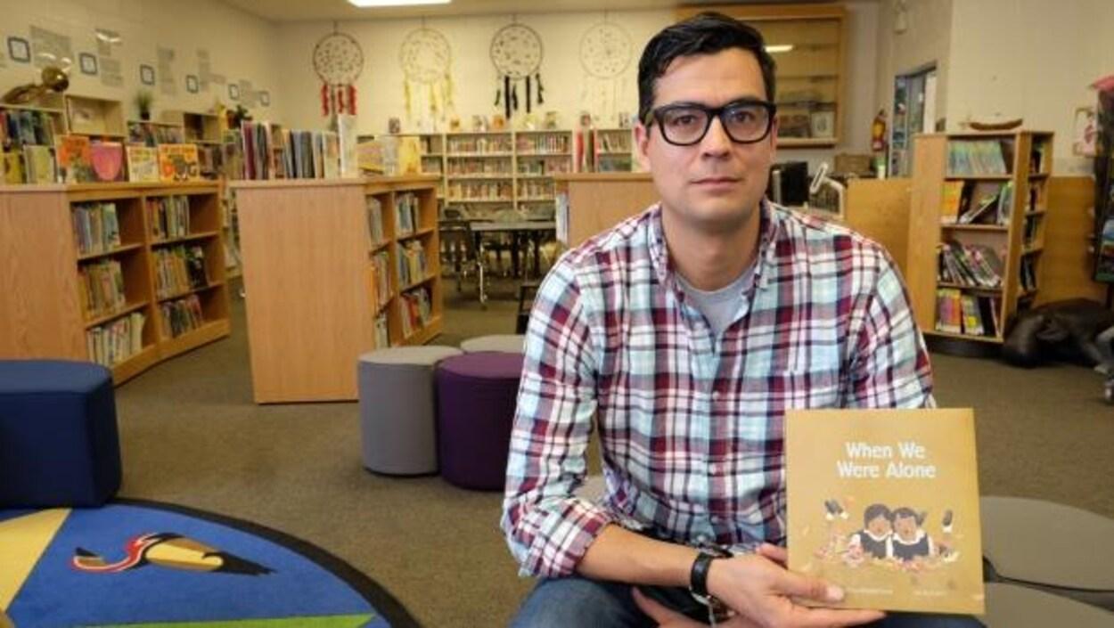 David A. Robertson tient une copie de When We Were Alone dans une bibliothèque.