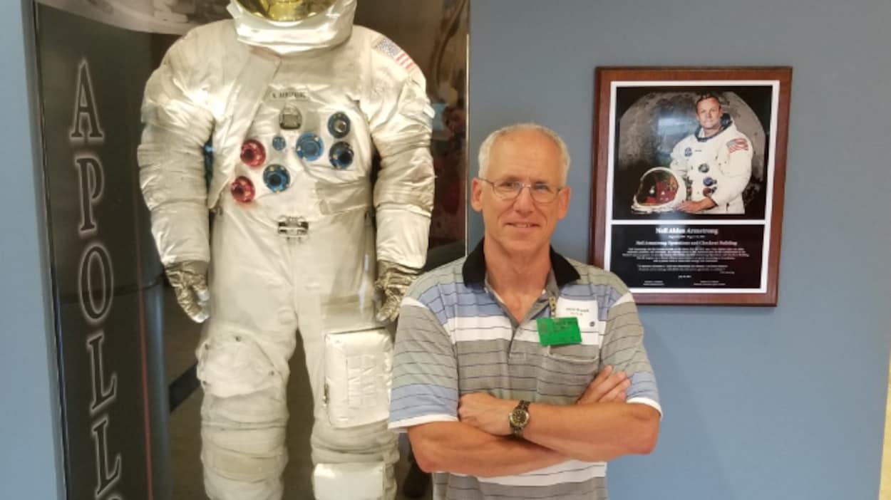 David Brault souriant à côté d'un habit d'astronaute.