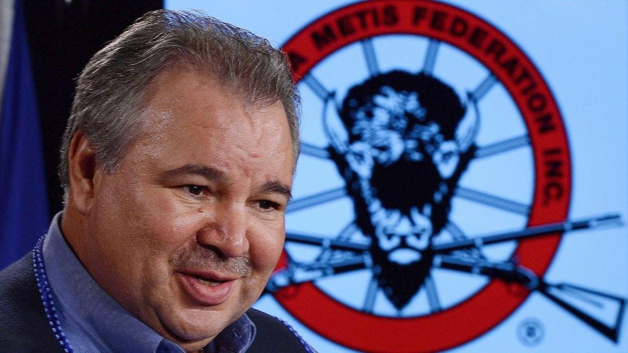 Un homme pose devant le logo de la FMM, sur lequel figurent une tête de buffle et deux carabines.