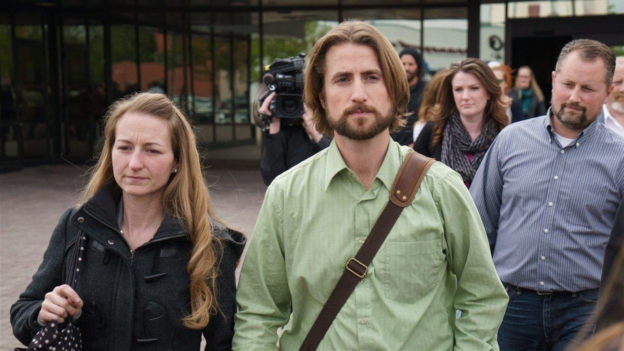 Une femme tient un homme par la main. Ils sont suivi de plusieurs personnes dont un cameraman.