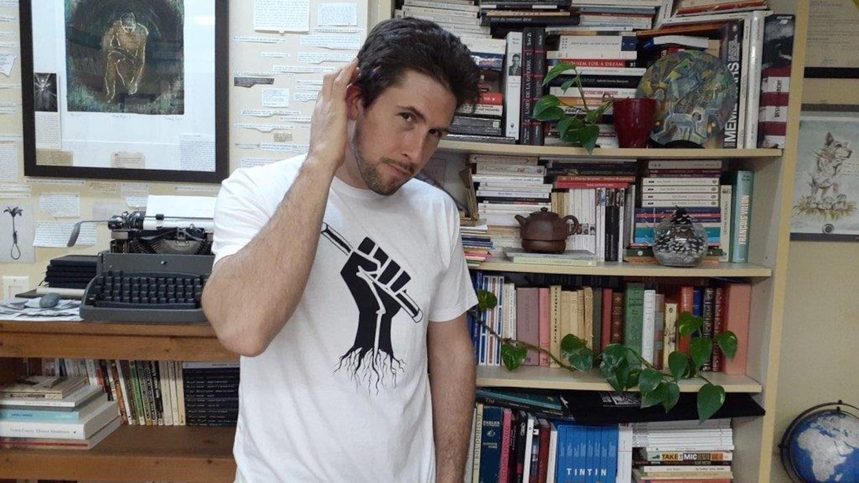 David Goudreault porte un t-shirt sur lequel est imprimé un poing levé portant un crayon.