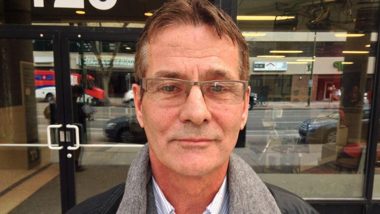 Un homme portant des lunettes debout sur un trottoir devant une porte.