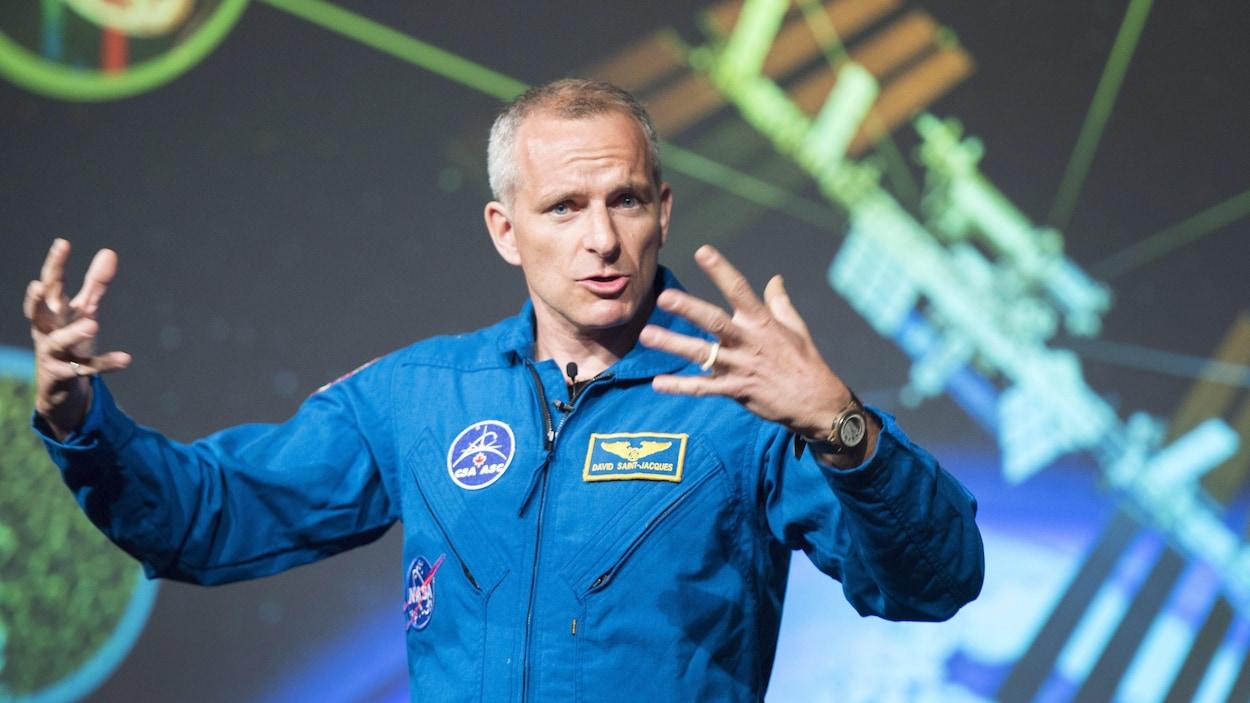 L'astronaute David Saint-Jacques, vêtu de son uniforme à l'effigie de l'Agence spatiale canadienne, donne une conférence qui porte sur son départ vers la Station spatiale internationale.