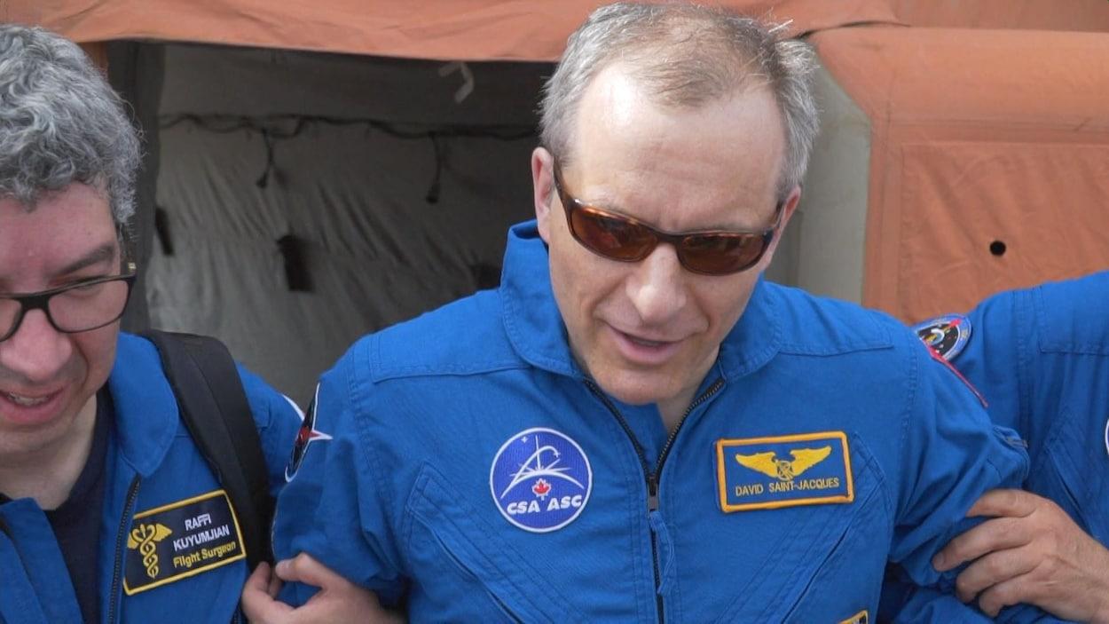 L'astronaute canadien David Saint-Jacques parle aux médias soutenu debout par des collègues.
