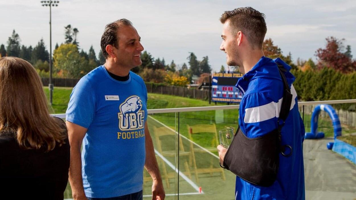 Une homme avec un chandail UBC Football parle avec un joueur de football sur le terrain.