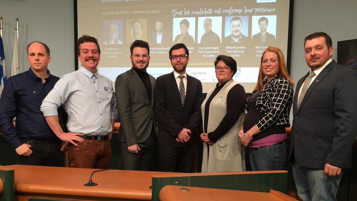 Les sept candidats prennent la pose pour une photo de groupe.