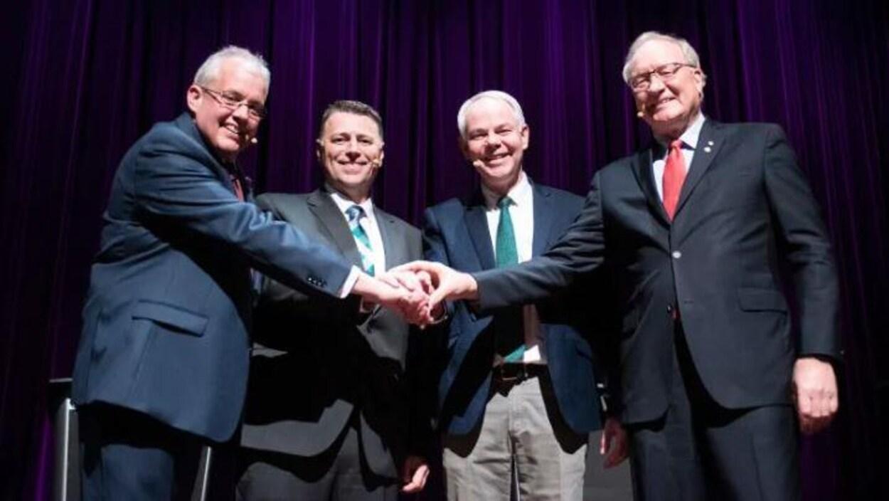 Quatre hommes vêtus de complets, debout sur une scène, se donnent la main devant un rideau.