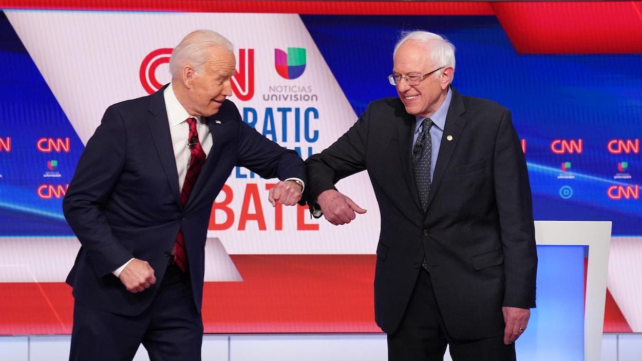Joe Biden et Bernie Sanders se donnant un coup de coude.