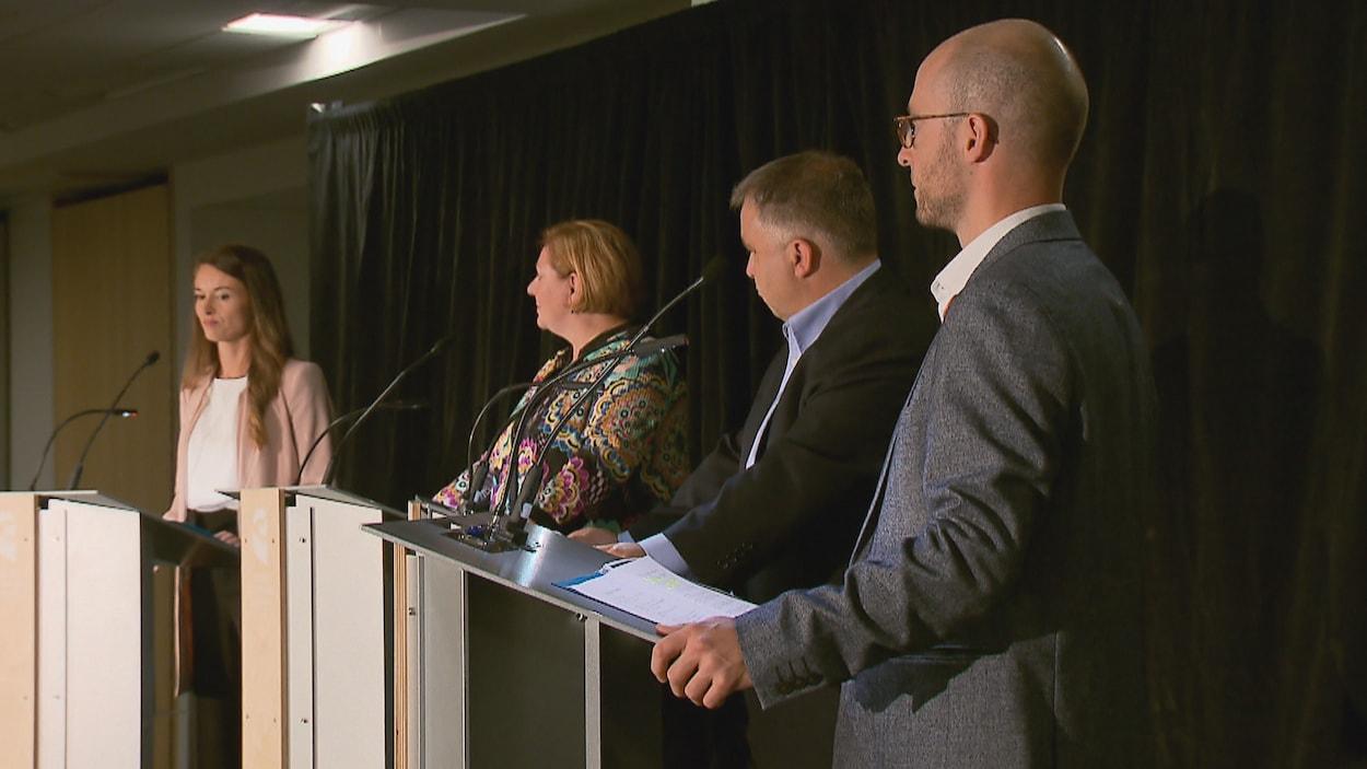 Les quatre participants au débat écoutent une question posée par l'animateur des échanges, le journaliste Pierre Jobin. Les candidats se tiennent debout derrière un lutrin. On aperçoit, de gauche à droite : Joëlle Boutin, Diane Lavallée, Sébastien Proulx et Sol Zanetti.