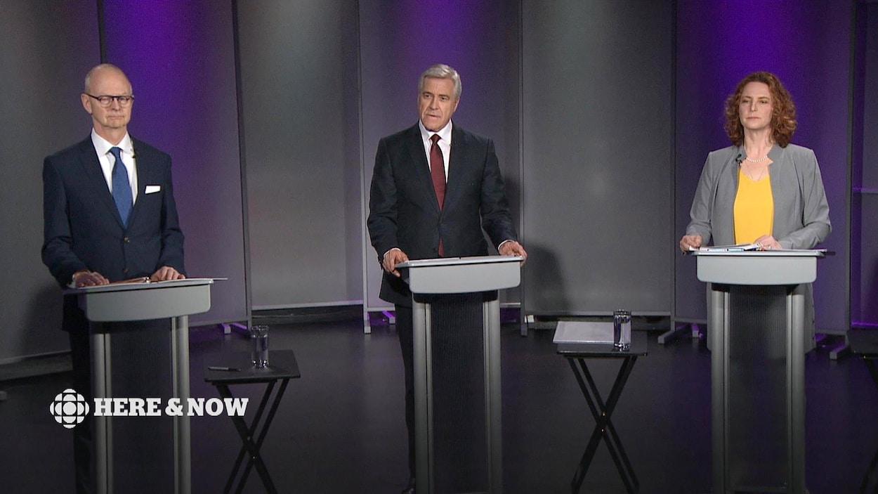 Les trois chefs sont debouts derrière des podiums.