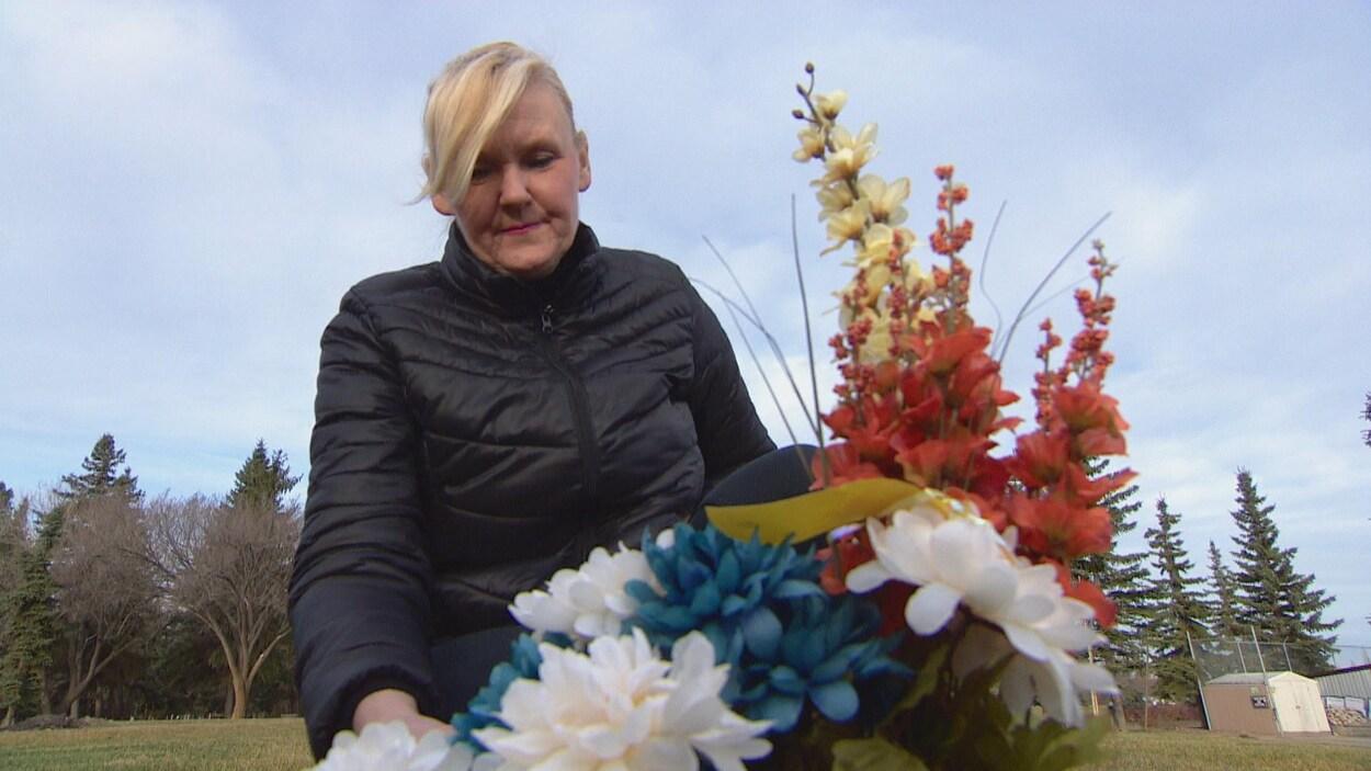Debb Cooper une amie de l'artiste peintre Sterling Gauthier se recueille sur sa tombe, derrière un bouquet de fleurs.