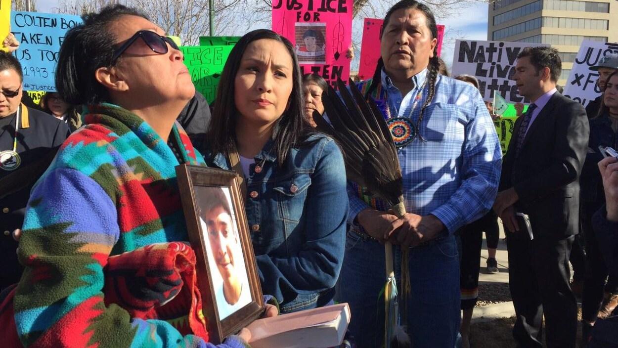 Debbie Baptiste et Jade Tootoosis sont entourées par des manifestants brandissant des pancartes, la mère tient un portrait de Colton Boushie.