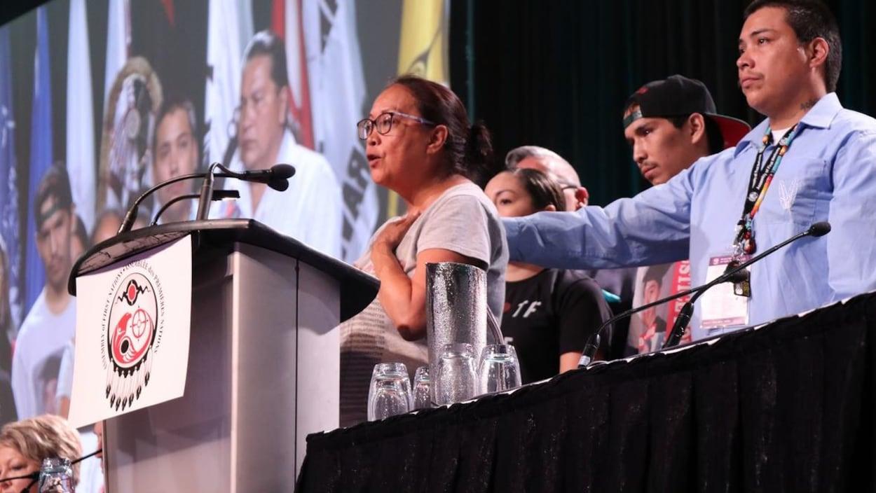 La mère de Colten Boushie fait un discours. Sa main gauche est posée sur son coeur, son visage est ému. Des gens se tiennent derrière elle, dont un homme qui pose une main dans le dos de la mère en signe de soutien.