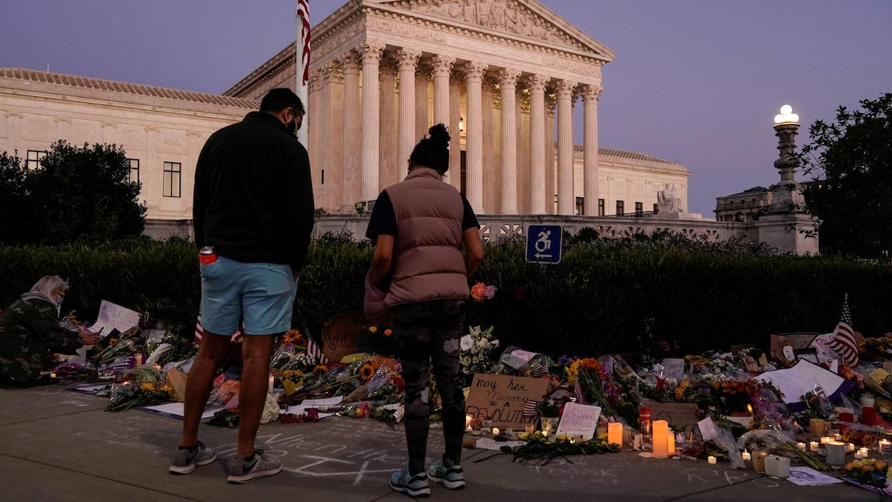 Un homme et une femme, devant des gerbes de fleurs déposées à proximité de la Cour suprême.
