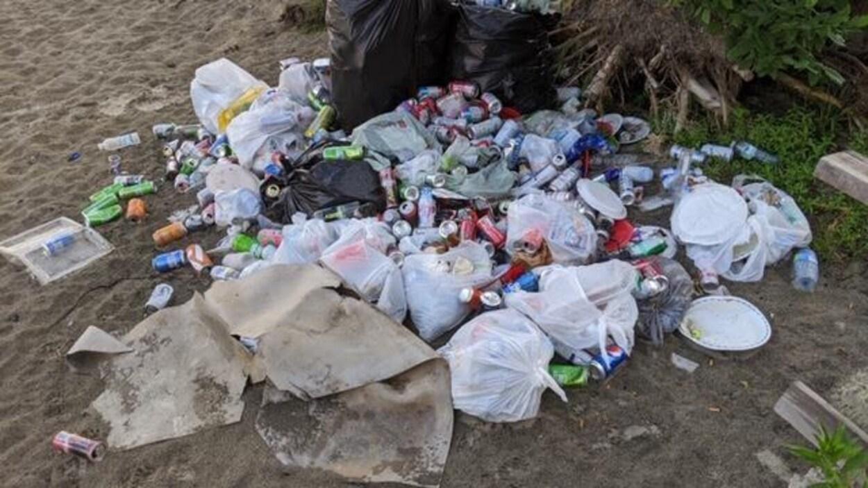 Une pile de déchets en tout genre et de sacs de poubelles sur une plage.
