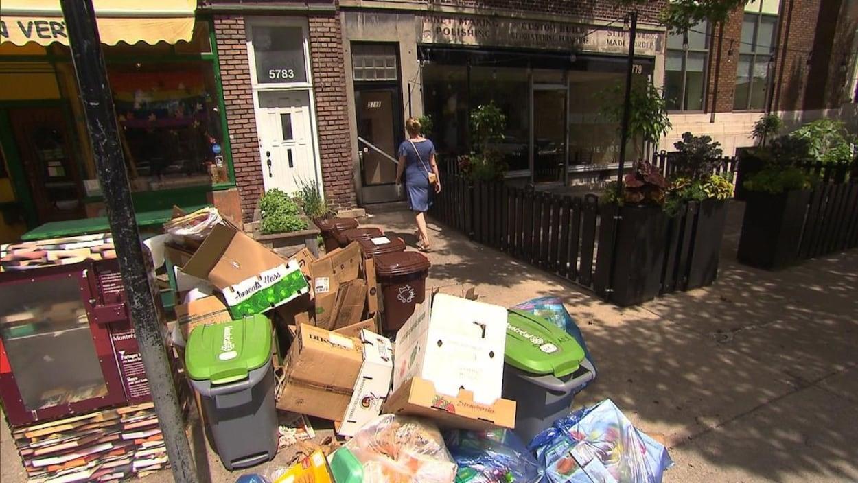Des piles de boîtes en carton, de bacs verts et de bacs bruns en bordure de la rue.