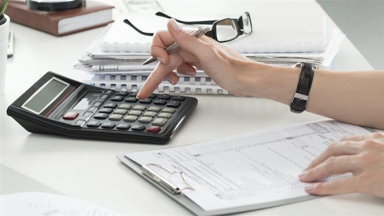 Une femme remplit une déclaration de revenus à l'aide d'une calculatrice.