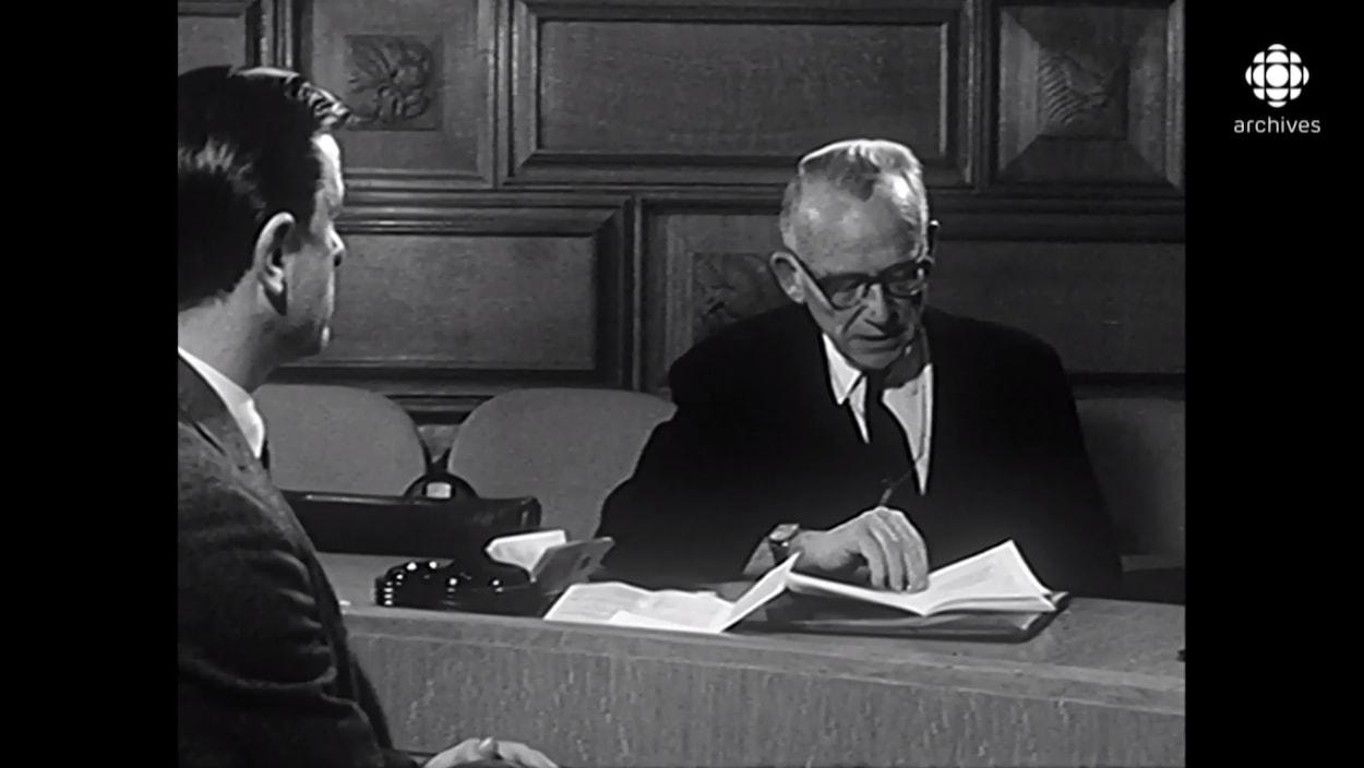 L'avocat canadien John Humphrey, assis à une table, lit la Déclaration universelle des droits de la personne.