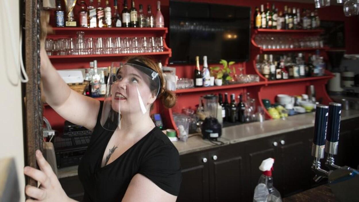 Une femme portant un masque arrange le comptoir de son restaurant.