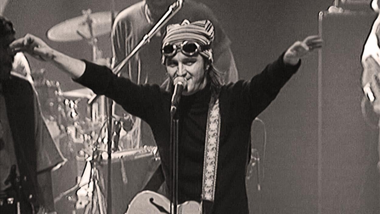 L'homme tend les bras sur scène devant un micro.