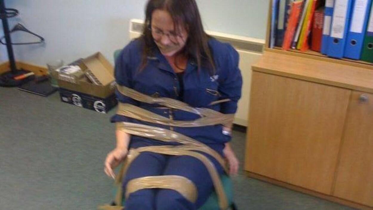 DeeAnn Fitzpatrick ligotée à une chaise et bâillonnée avec du ruban adhésif brun.