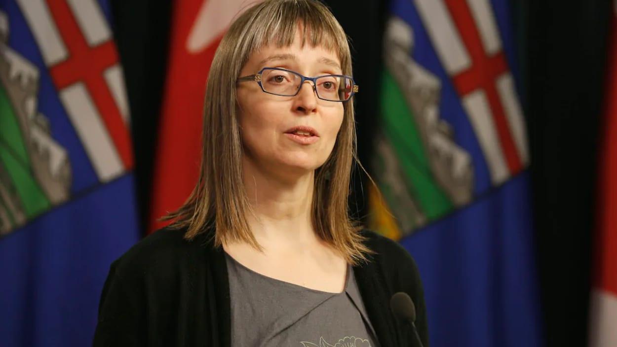 Deena Hinshaw parle devant les drapeaux canadien et albertain de la salle des médias de l'Assemblée législative.