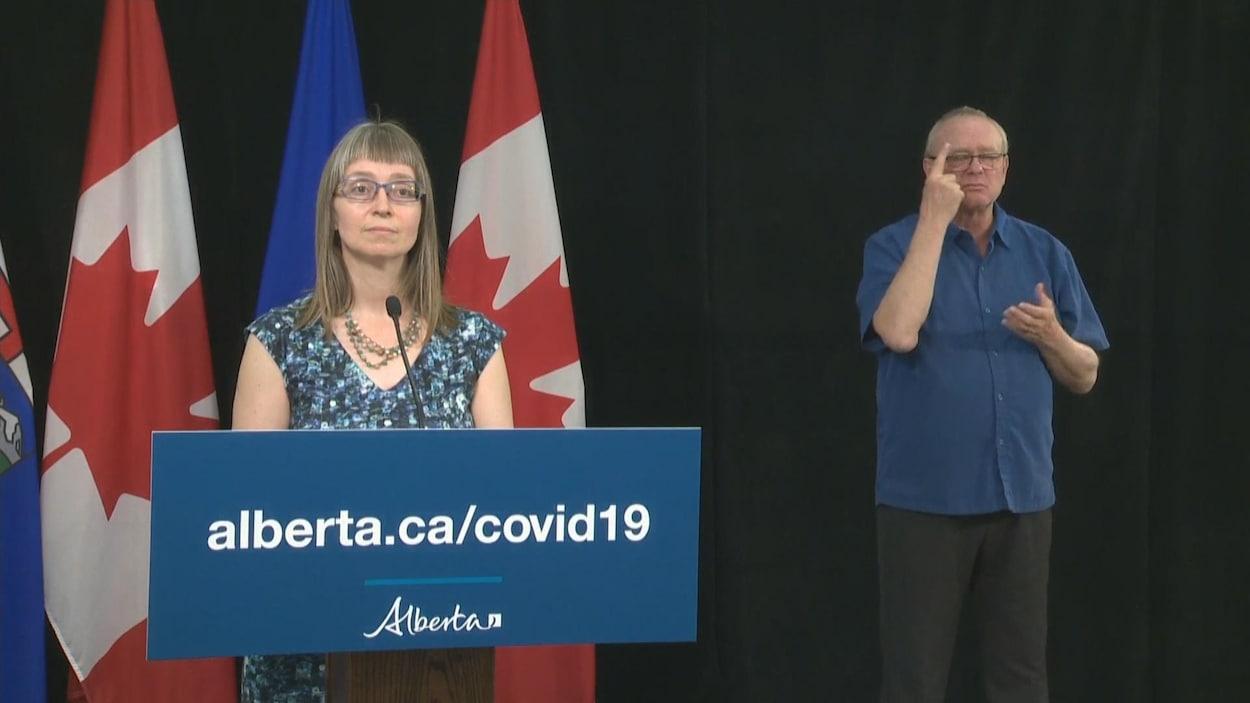Deena Hinshaw au micro accompagné par l'interprète de la langue des signes.