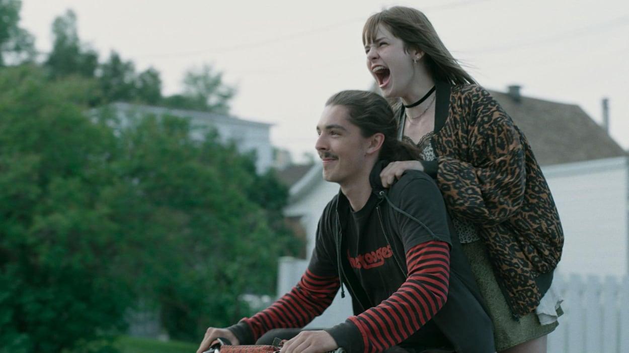 Une jeune fille est debout sur un vélo conduit par un garçon et crie