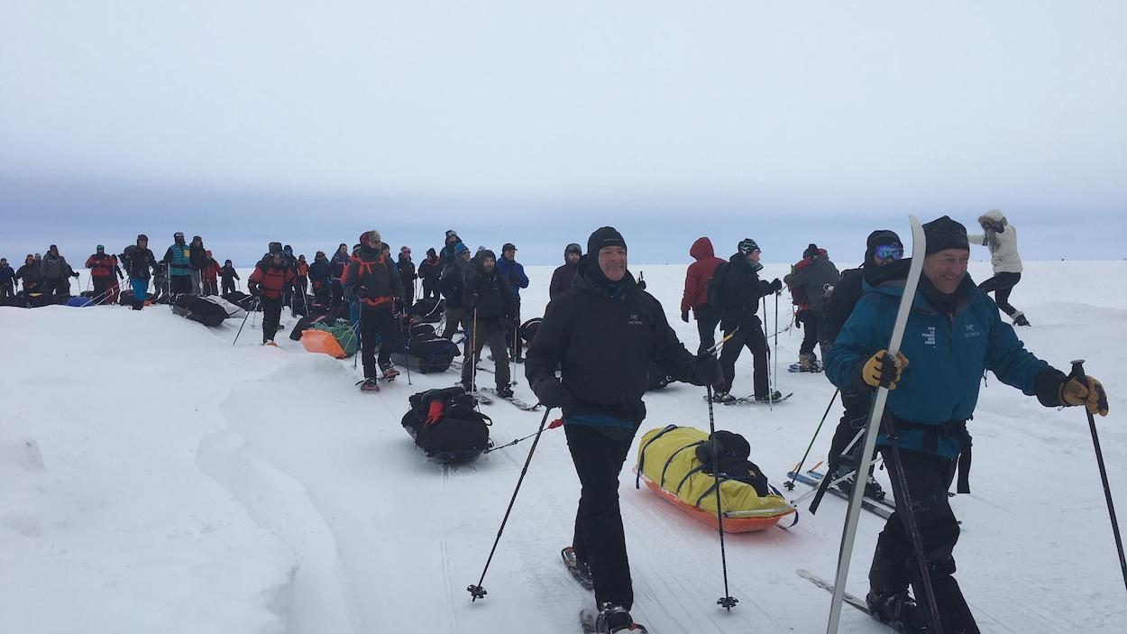 Des dizaines de personnes marchent avec leurs bagages sur le lac Saint-Jean.