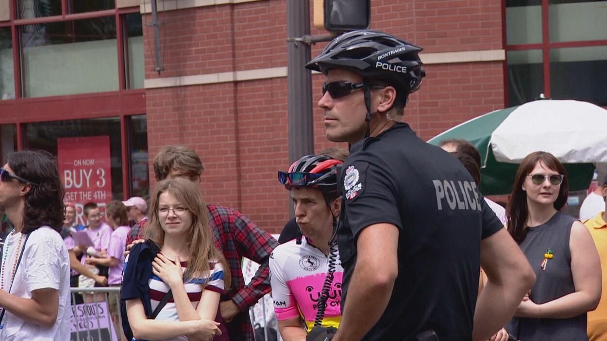 Un policier est de profil à la caméra. Il porte un casque et un chandail d'uniforme noir. En arrière, quelques passants.