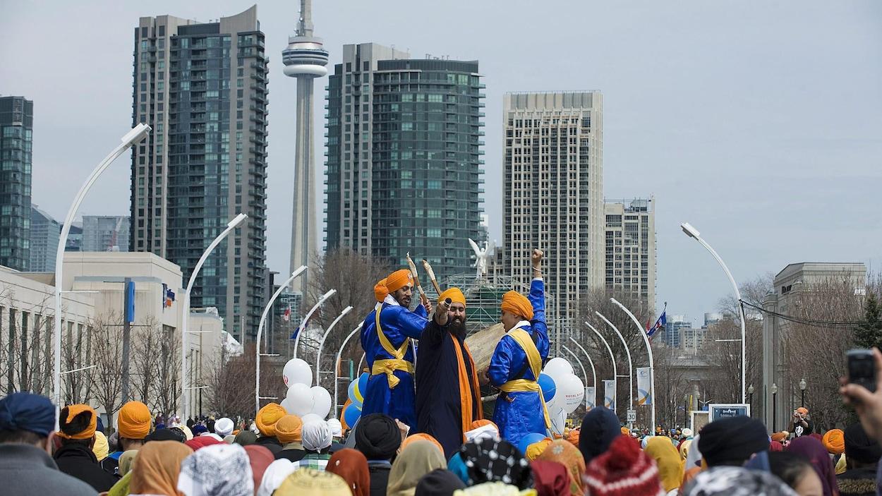 Un défilé avec le centre-ville de Toronto et la Tour CN en arrière-plan