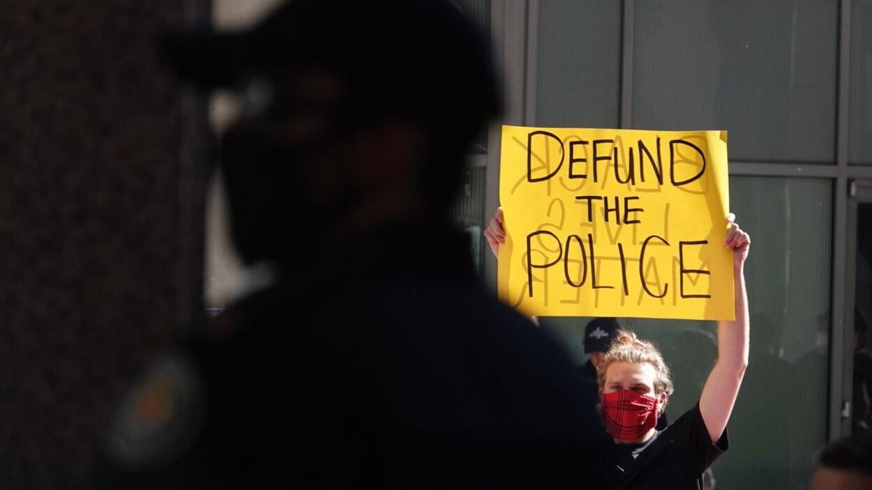 Un homme tient une pancarte sur laquelle est écrit « Defund the police » devant un policier.