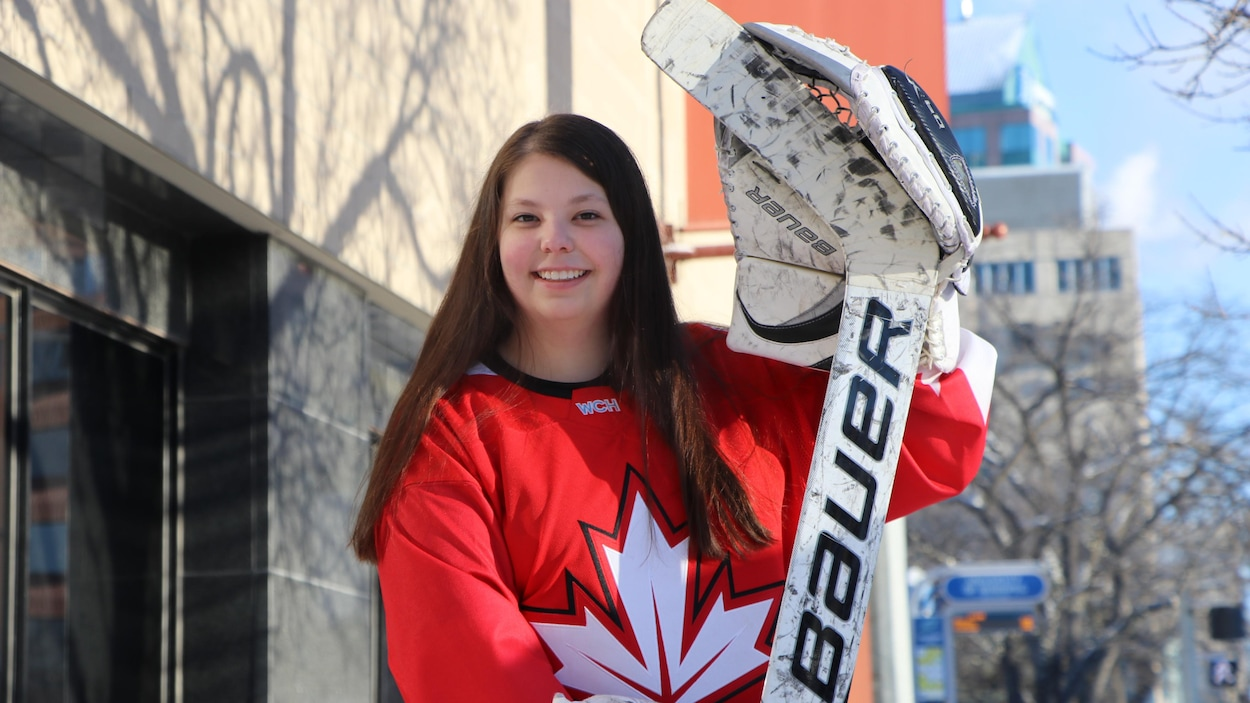 Delaney Jost porte son équipement de gardienne de but de hockey.