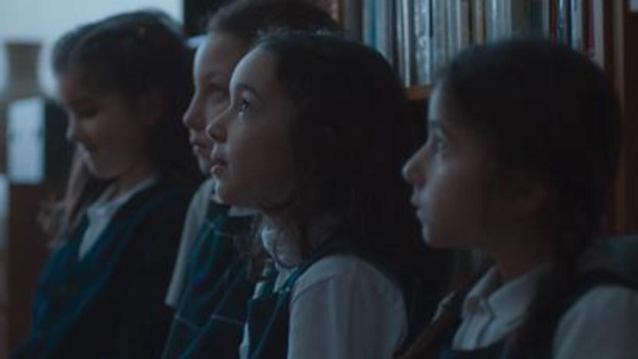 Quatre petites filles portant un uniforme scolaire.