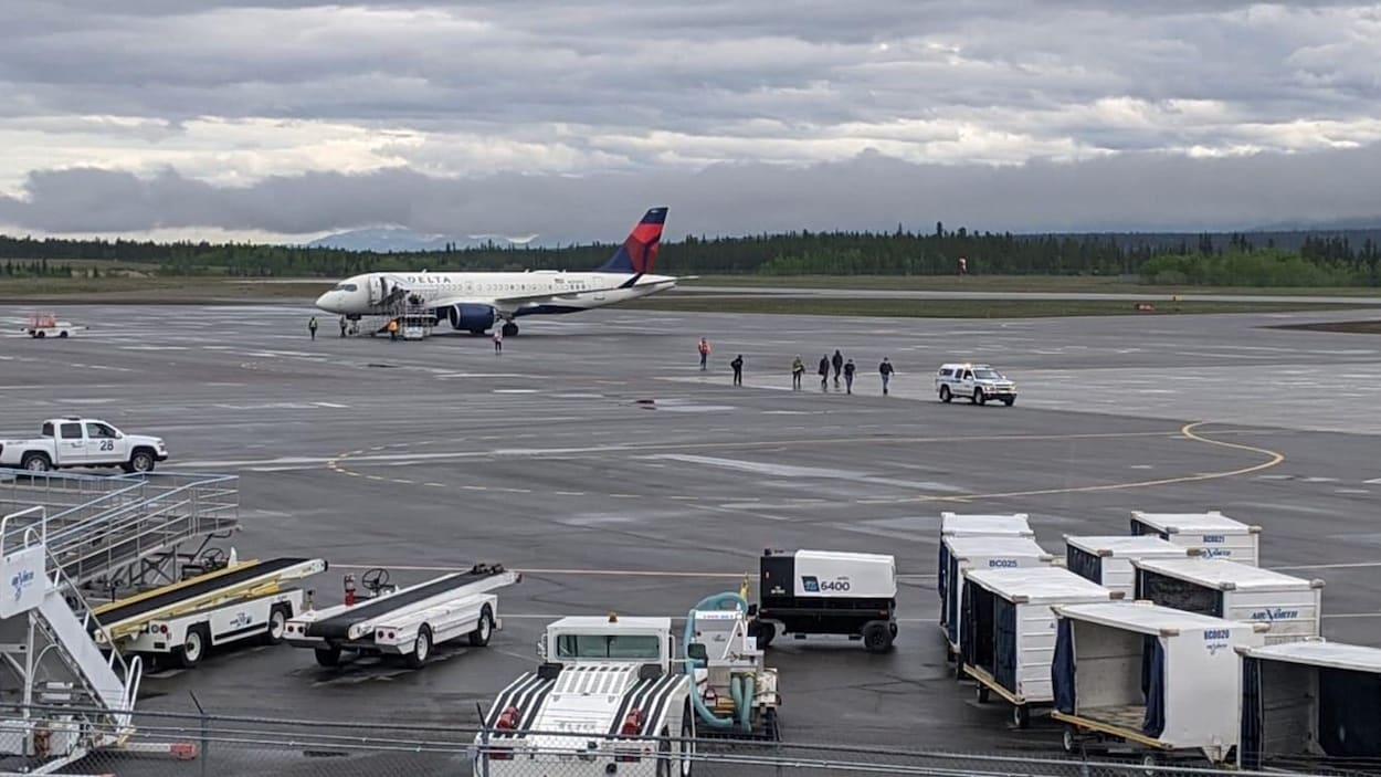 L'avion de Delta est garé sur le tarmac à Whitehorse pendant que neuf personnes se trouvent dehors sous un ciel nuageux.