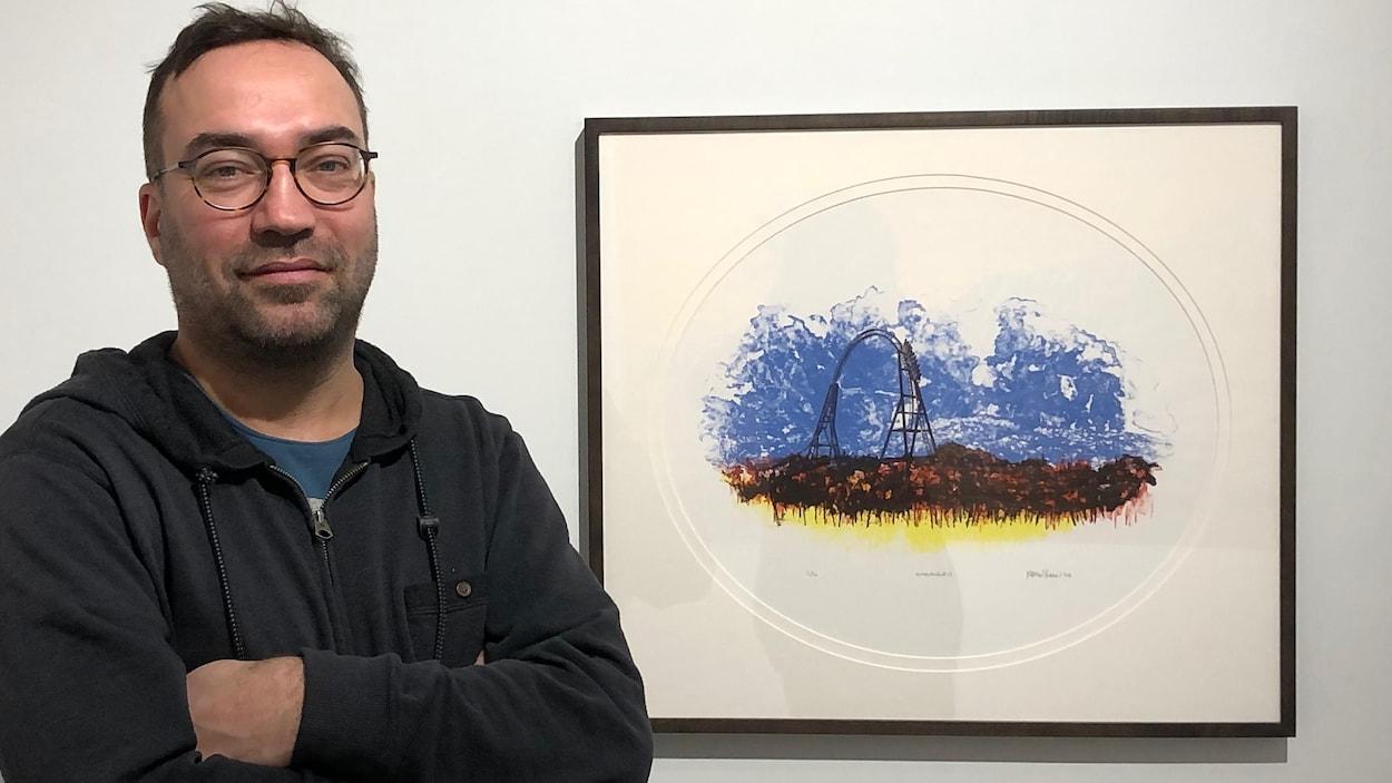 Tirée en 50 exemplaires, la toute première lithographie de l'artiste Martin Bureau servira à amasser des fonds pour le projet Demain, la forêt.  Un homme, aux bras croisés, pose à côté d'une oeuvre accrochée au mur.