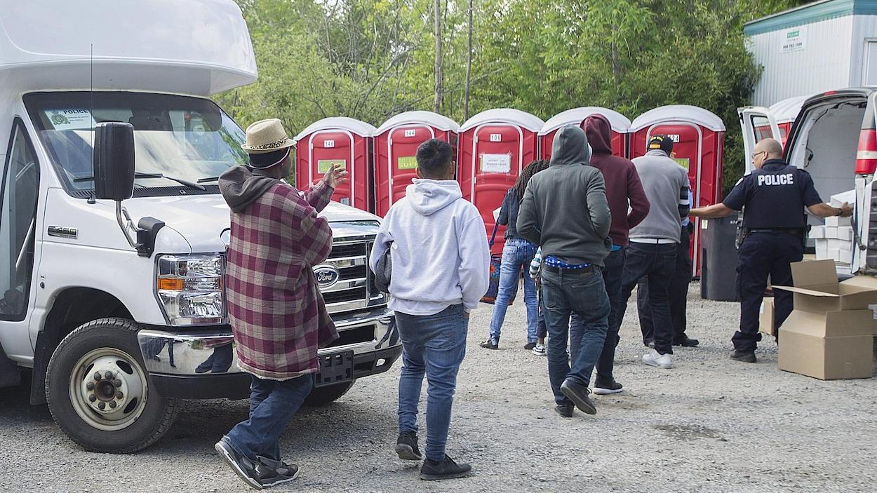 Six demandeurs d'asile arrivés par le chemin Roxham, près de Saint-Bernard-de-Lacolle, reçoivent des boîtes à lunch des mains d'un policiers, alors qu'on voit des toilettes chimiques en arrière-plan.