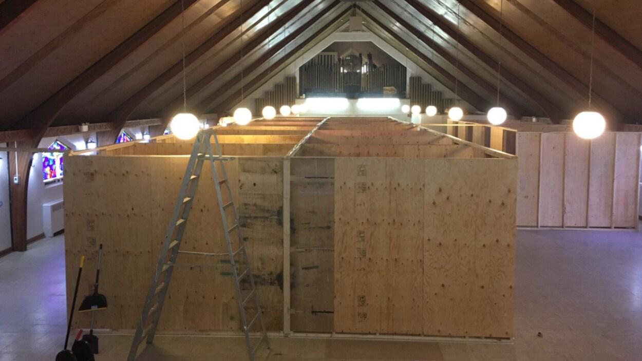 De larges panneaux de contreplaqué délimitent des chambres individuelles de fortune dans une église.