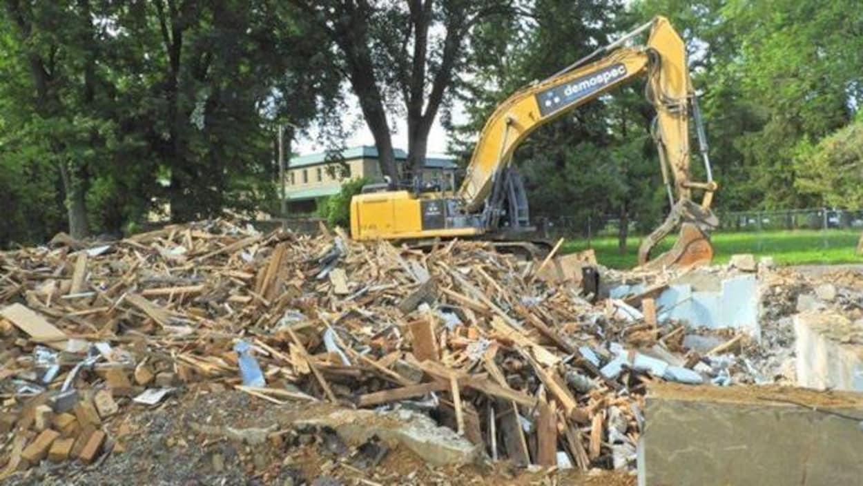 Les décombres de la Maison Pelland à côté d'une grue