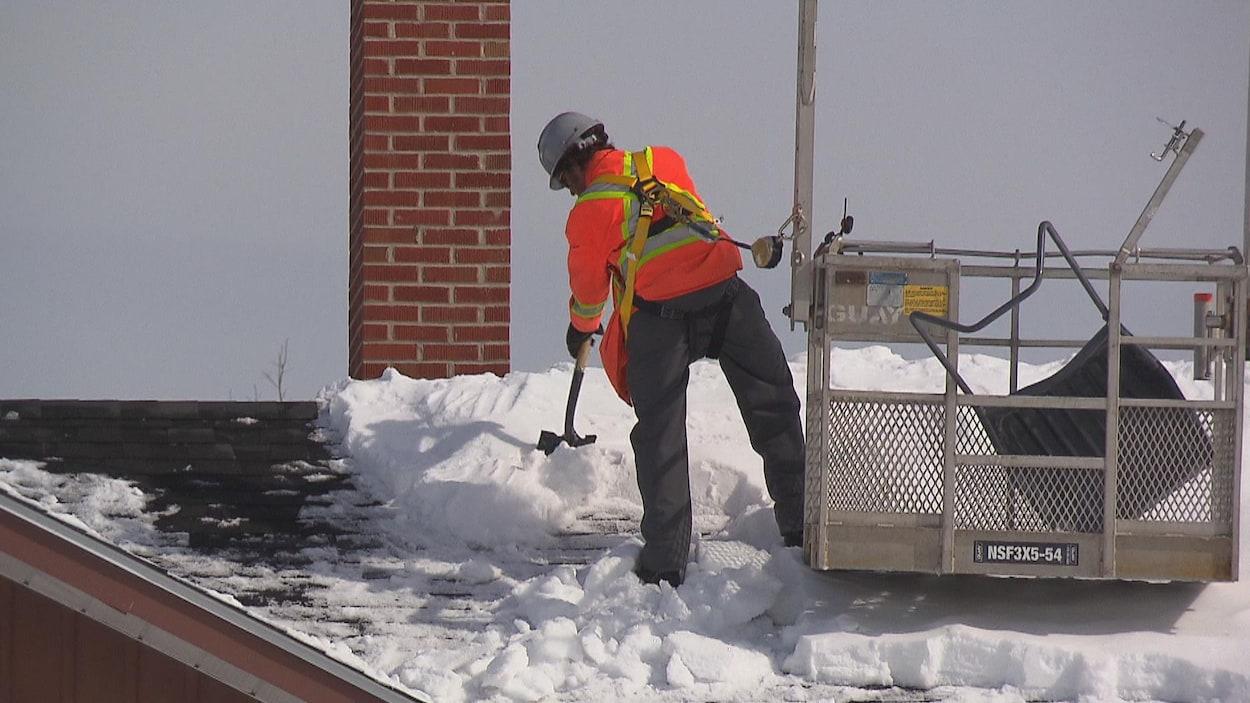 Un travailleur s'affaire à déneiger le toit d'un édifice.