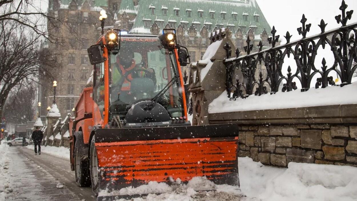 Une déneigeuse sur le trottoir de la rue Wellington, devant le parlement d'Ottawa.