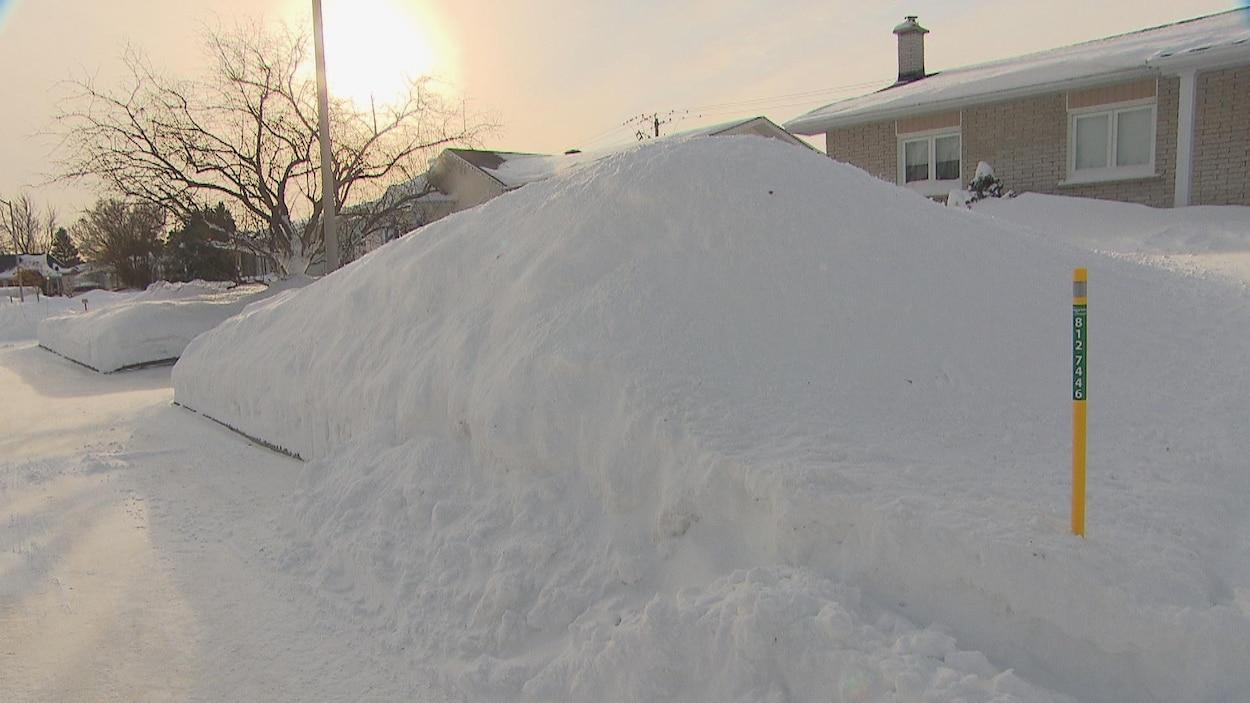 Un important banc de neige devant une maison de Saguenay.