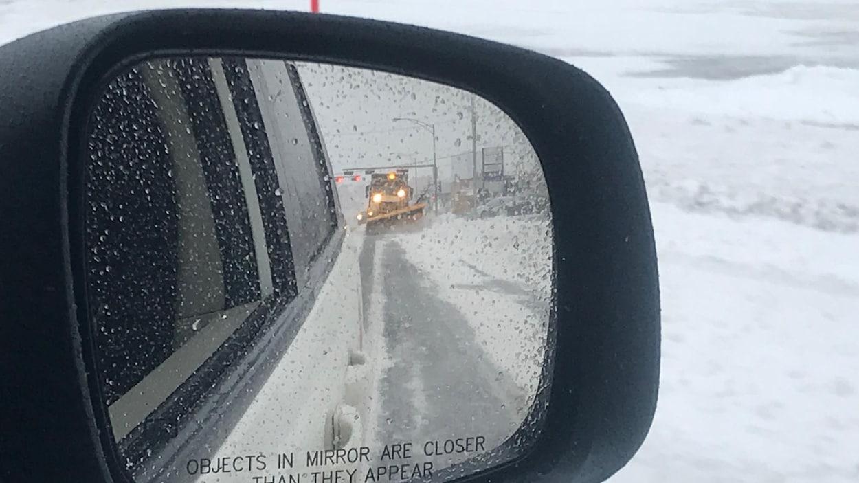 Un véhicule de déneigement vue à partir du rétroviseur d'une voiture