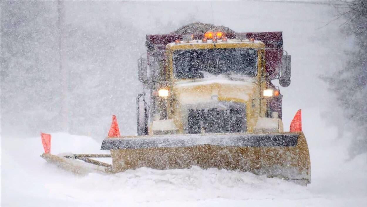 Un camion de déneigement dégage une route dans la tempête