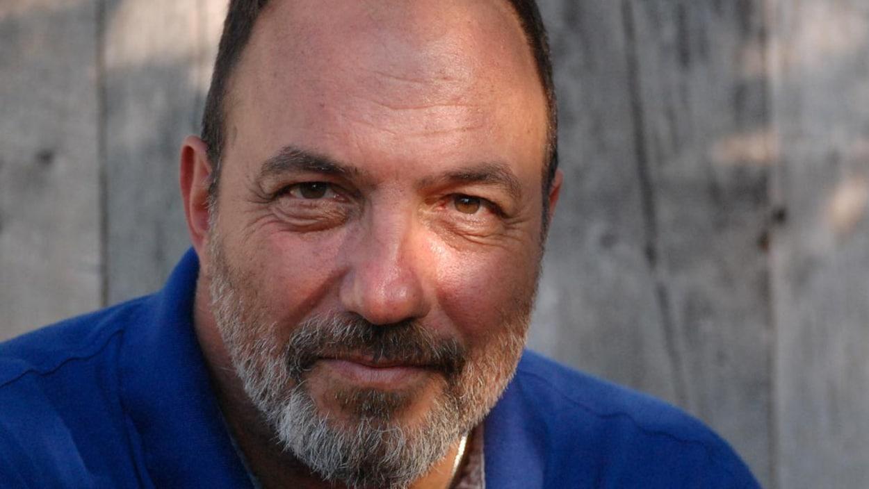 L'homme vêtu d'un chandail bleu regarde la caméra.