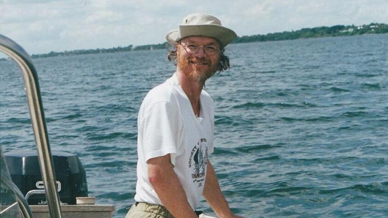On voit le professeur sur un bateau vétu d'un chapeau et de lunettes de vue.